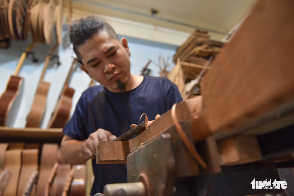 Buu Thang shapes a guitar's neck to fit a customer's order. Photo: Ngoc Phuong/Tuoi Tre
