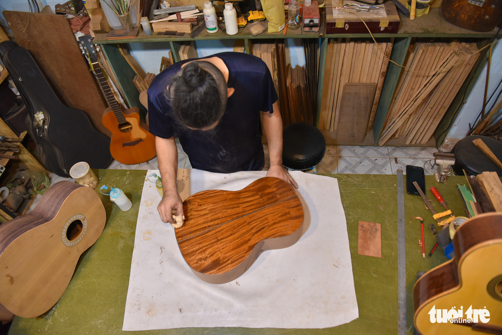 Buu Thang paints a sound box which decides how good a guitar will look. Photo: Ngoc Phuong/Tuoi Tre