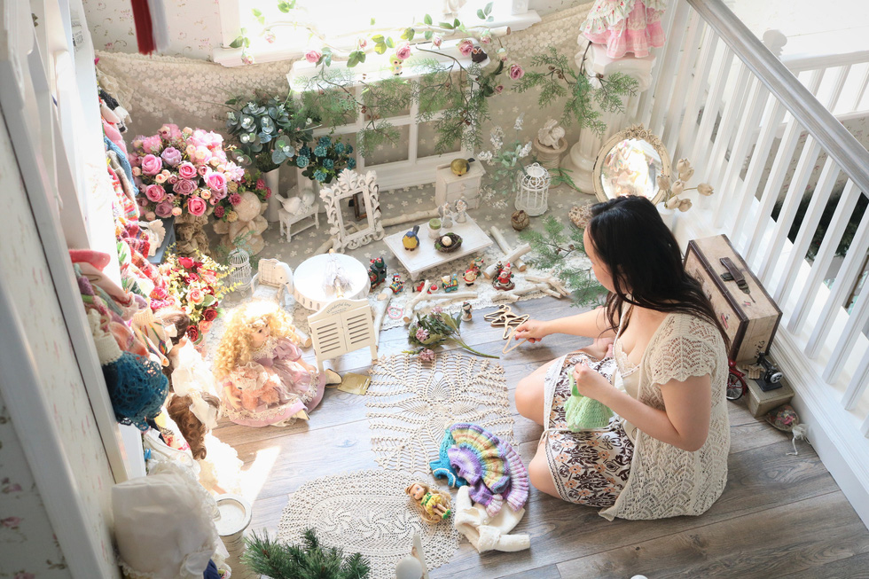 Phung Le Lan Thanh sits beside a corner displaying various kinds of dolls that she and her husband have collected during the past years. Photo: Hoang An / Tuoi Tre