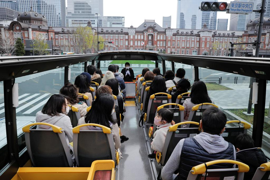 Passengers wearing protective face masks enjoy the viewing of Tokyo Station building from an open-top sightseeing bus, operated by Hato Bus Co., after Japan's government lifted the coronavirus disease (COVID-19) state of emergency in the Tokyo area, in Tokyo, Japan March 22, 2021. Photo: Reuters