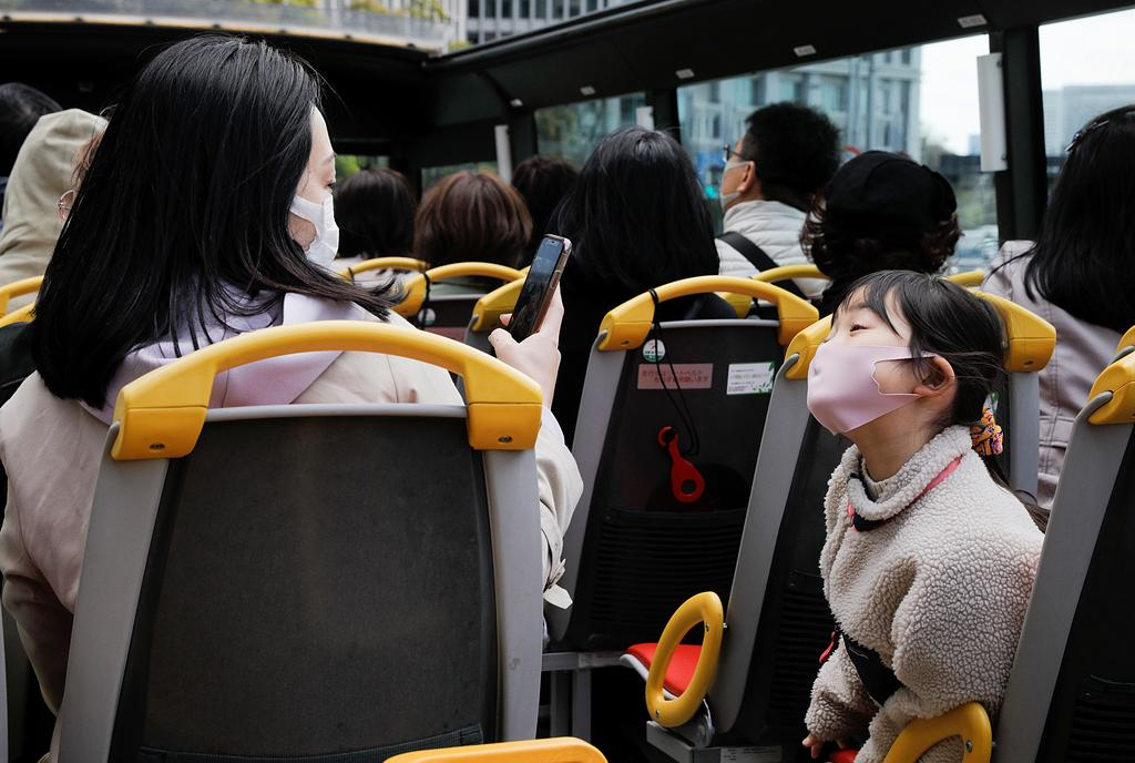 A child wearing a face mask poses for a picture as passengers enjoy an open-top sightseeing bus tour, operated by Hato Bus Co., as the tour service resumed after Japan's government lifted the coronavirus disease (COVID-19) state of emergency in the Tokyo area, in Tokyo, Japan March 22, 2021. Photo: Reuters
