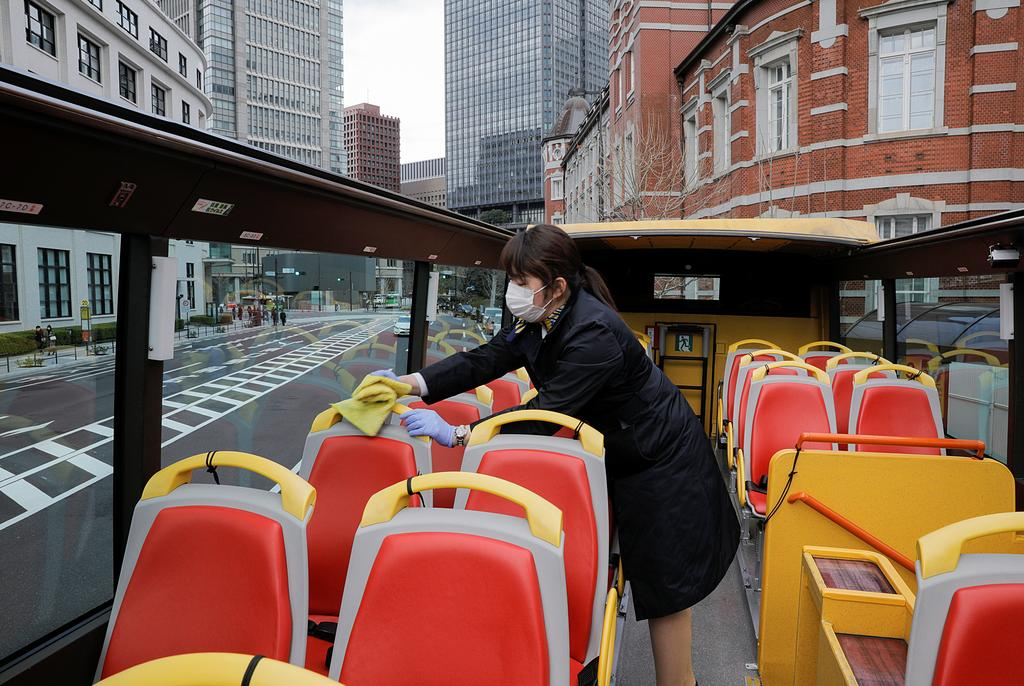 A tour guide of Hato Bus Co. disinfects seats of an open-top sightseeing bus, as the tour service resumed after Japan's government lifted the coronavirus disease (COVID-19) state of emergency in the Tokyo area, in Tokyo, Japan March 22, 2021. Photo: Reuters