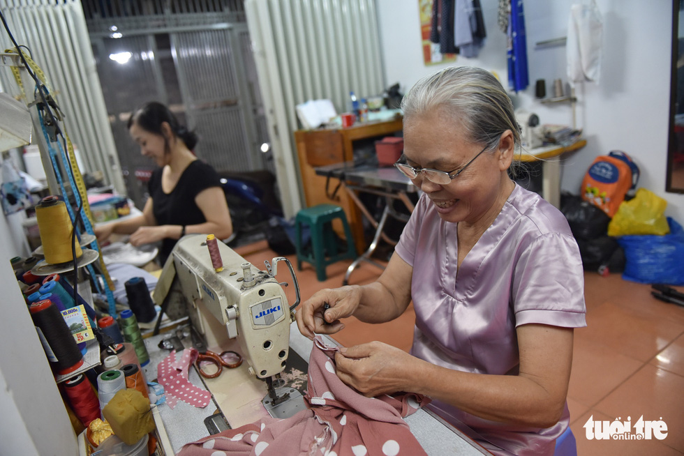 Le Thi Be (front) and her daughter-in-law Tran Thi Hong Thi are doing their jobs as tailors during the daytime before becoming teachers of disadvantaged children in the afternoon. Photo: Ngoc Phuong / Tuoi Tre