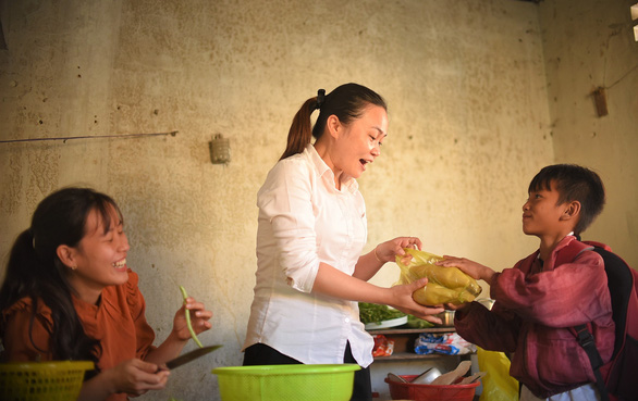 Student Dinh Van Phuoc of Canh Tien Primary School gives his teachers some home-cooked corn. – Photo: Lam Thien/Tuoi Tre