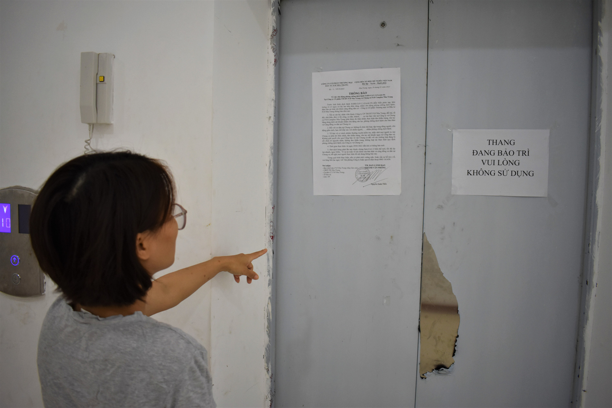 A woman points her finger at a shuttered elevator at the P.H Nha Trang apartment complex in Nha Trang City, Khanh Hoa Province, Vietnam. Photo: Minh Chien / Tuoi Tre