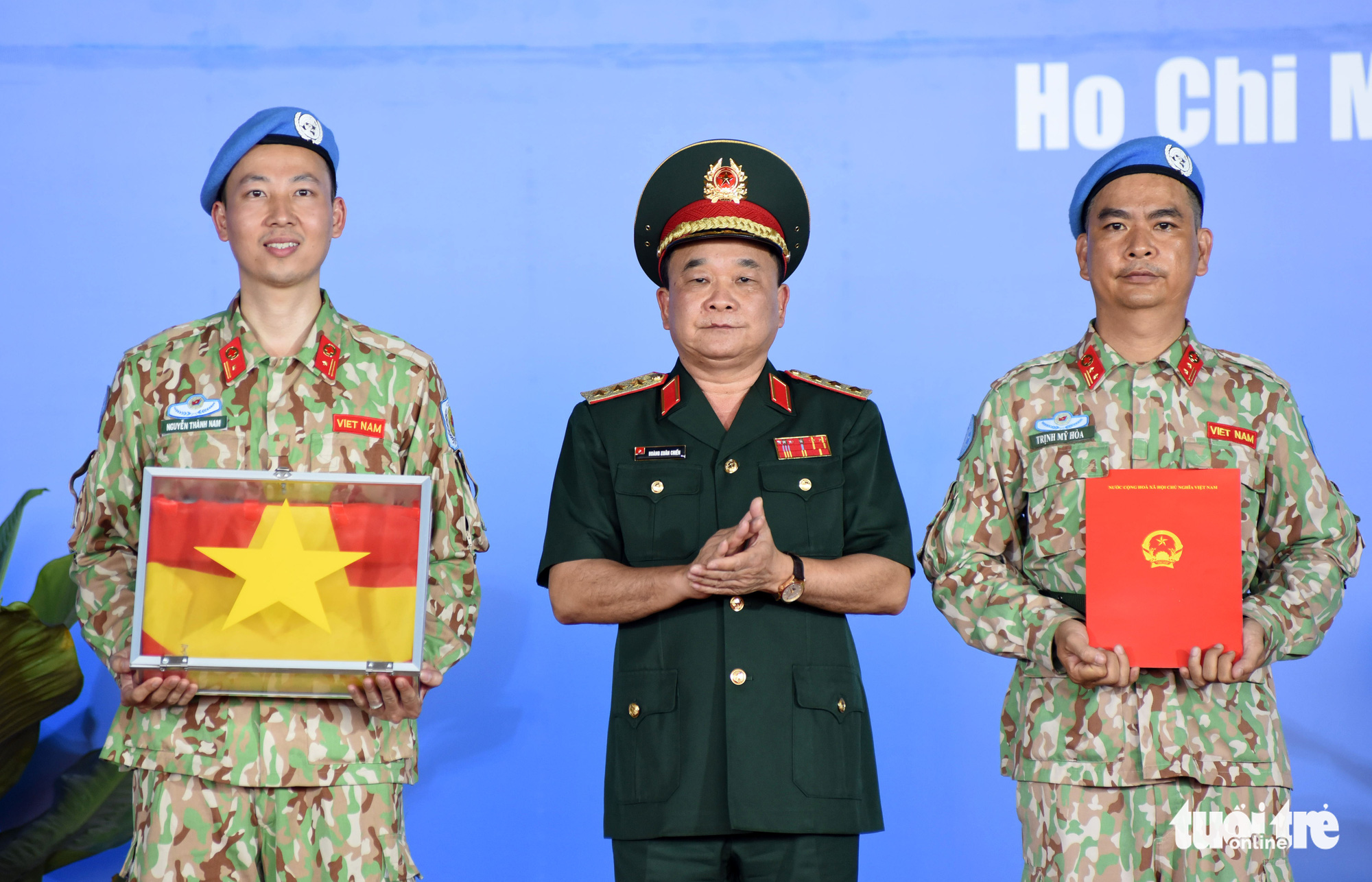 Deputy Minister of National Defense Hoang Xuan Chien hands souvenirs and national flags to soldiers of the third Level-2 Field Hospital during a ceremony in Ho Chi Minh City, March 23, 2021. Photo: Duyen Phan / Tuoi Tre