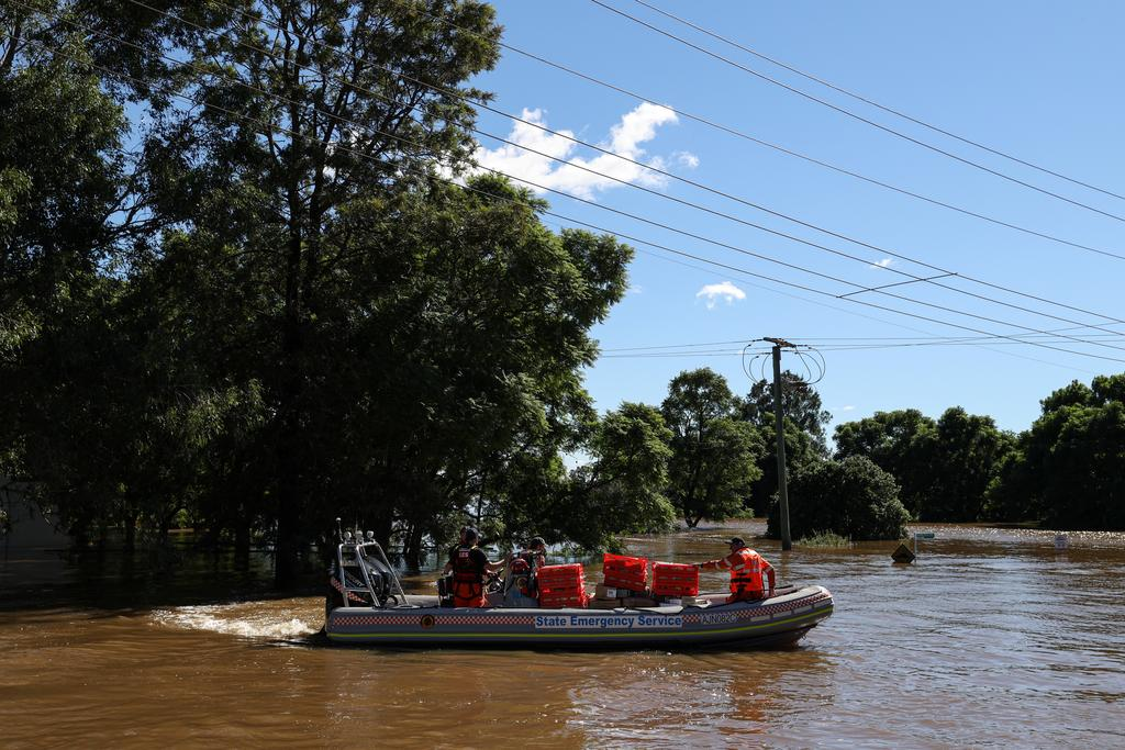 A State Emergency Service crew transports food to a stranded community only accessible by boat after days of heavy rain resulted in severe flooding, in western Sydney, Australia, March 24, 2021. Photo: Reuters