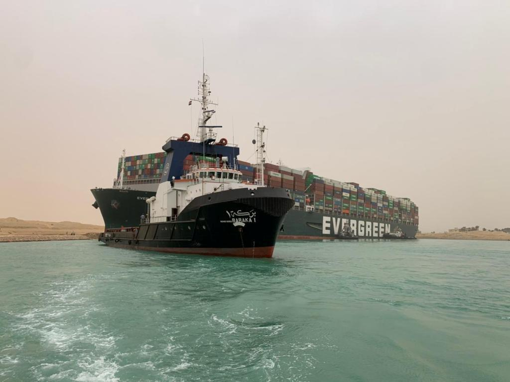 Tug boats work to free giant container ship stuck in Suez Canal