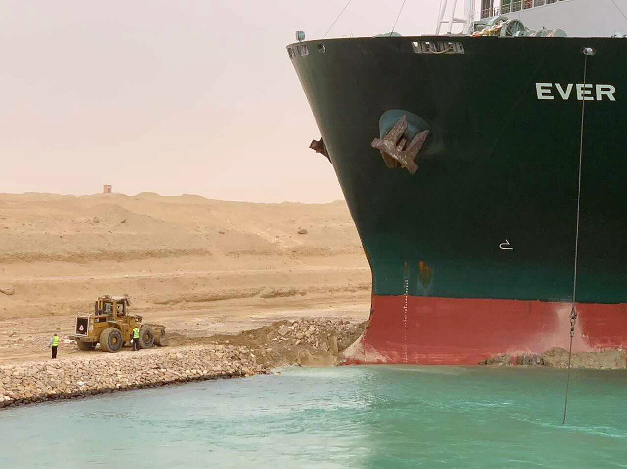 A handout picture released by the Suez Canal Authority on Wednesday shows a part of the MV Ever Given lodged sideways and blocking traffic on Egypt's Suez Canal.