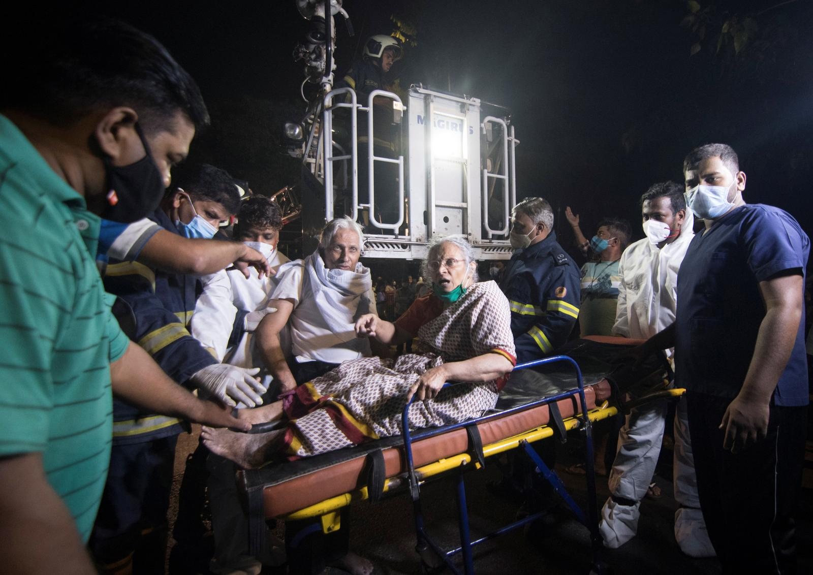People carry a woman on a stretcher towards a safer place after a fire broke out at a coronavirus disease (COVID-19) hospital in Mumbai, India, March 26, 2021. Photo: Reuters