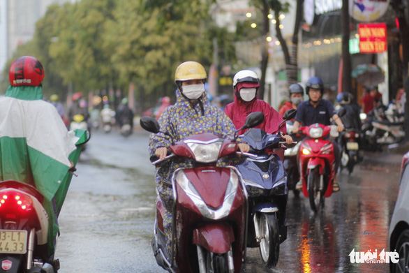 Commuters in Ho Chi Minh City navigate through the rain, March 25, 2021. Photo: Chau Tuan / Tuoi Tre