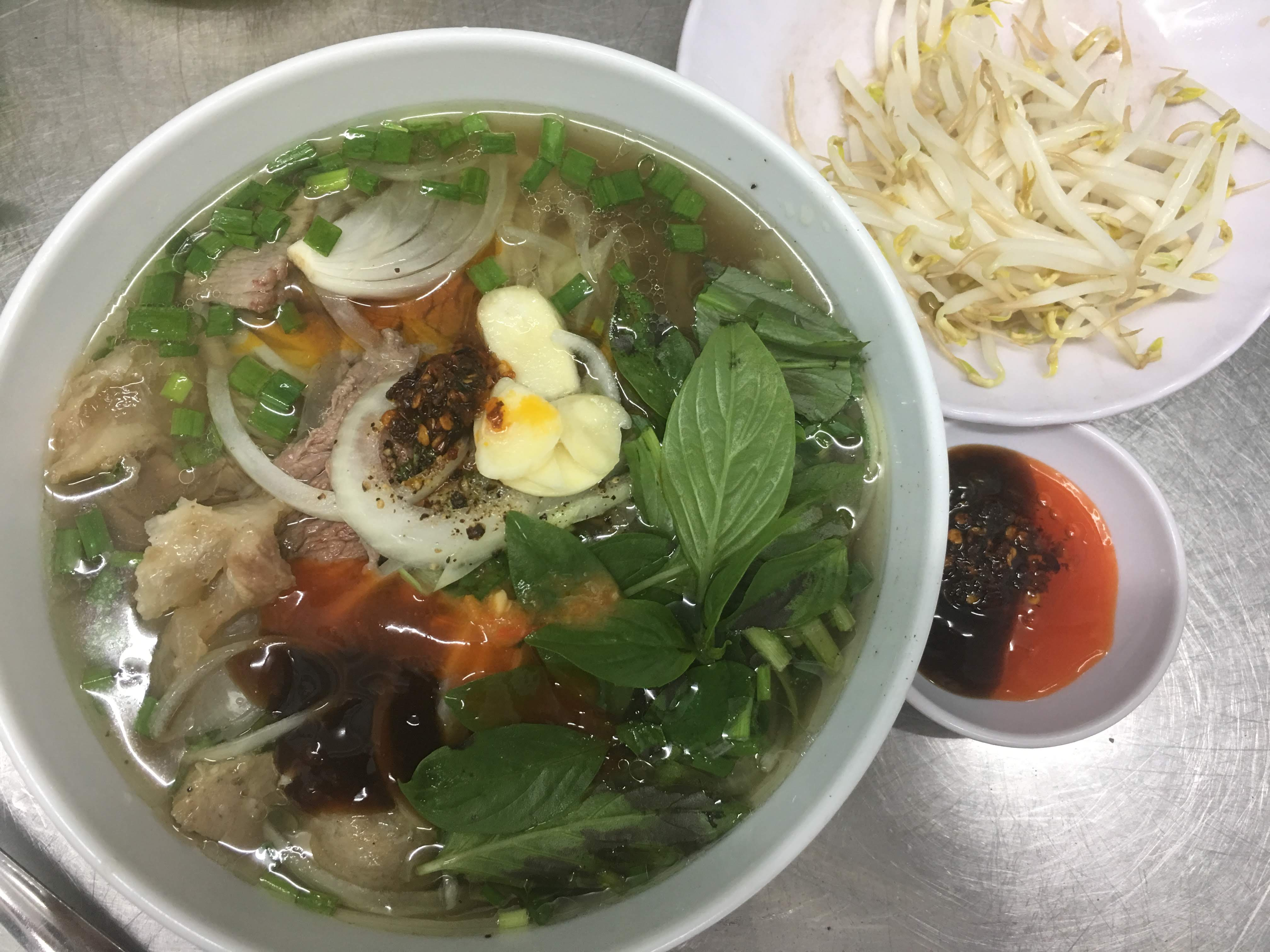 Southern-styled pho is served with mung bean sprouts, herbs and chili and hoisin sauces at a stall in Ho Chi Minh City's Phu Nhuan Street. Photo: Dong Nguyen / Tuoi Tre News