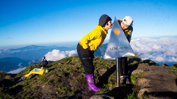 Two travelers pose on Mount of Lung Cu at 2,913m above sea level. Photo: Ng. Huong / Tuoi Tre
