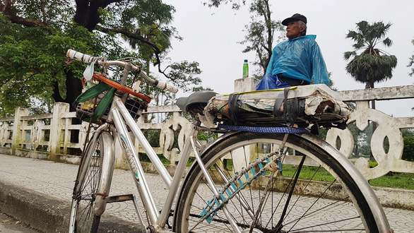Ton That Tam, a 70-year-old bicycle taxi driver, waits for potential customers on a daily basis at one end of Truong Tien Bridge, one of Hue City's landmarks. Photo: Nhat Linh / Tuoi Tre