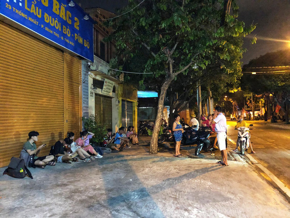 Residents sit on the sidewalk as related forces are investigating the scene of the fire in Thu Duc City, Ho Chi Minh City, Vietnam, March 30, 2021 – Photo: Chau Tuan / Tuoi Tre