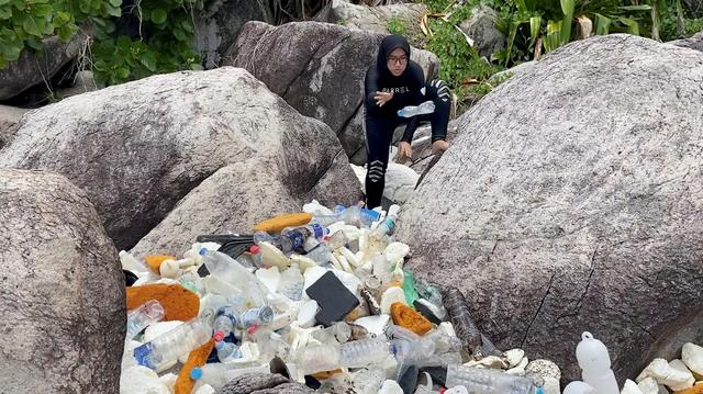 A woman clears trash by the sea at Tioman Island, Pahang, Malaysia, September 13, 2020, in this still image from video obtained via social media. Photo: The Monkey Project via Reuters