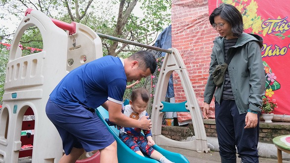 Duc watches a baby boy play with his father at Think Playgrounds' latest project in Phuc Tan, Hanoi on March 27. – Photo: Ha Thanh/Tuoi Tre