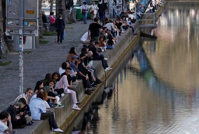 People enjoy a sunny and warm weather sitting along the Canal Saint-Martin in Paris amid the coronavirus disease (COVID-19) outbreak in France, March 31, 2021. Photo: Reuters