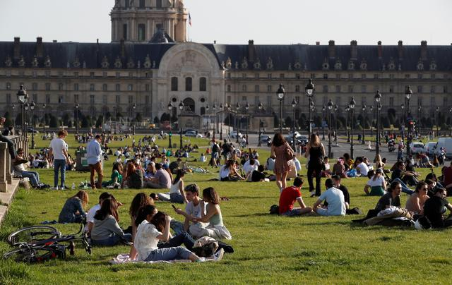People enjoy a sunny and warm weather sitting on the grass near the Invalides in Paris amid the coronavirus disease (COVID-19) outbreak in France, March 31, 2021. Photo: Reuters