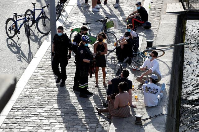 French police patrol as people enjoy a sunny and warm weather sitting along the banks of the River Seine in Paris amid the coronavirus disease (COVID-19) outbreak in France, March 31, 2021. Photo: Reuters