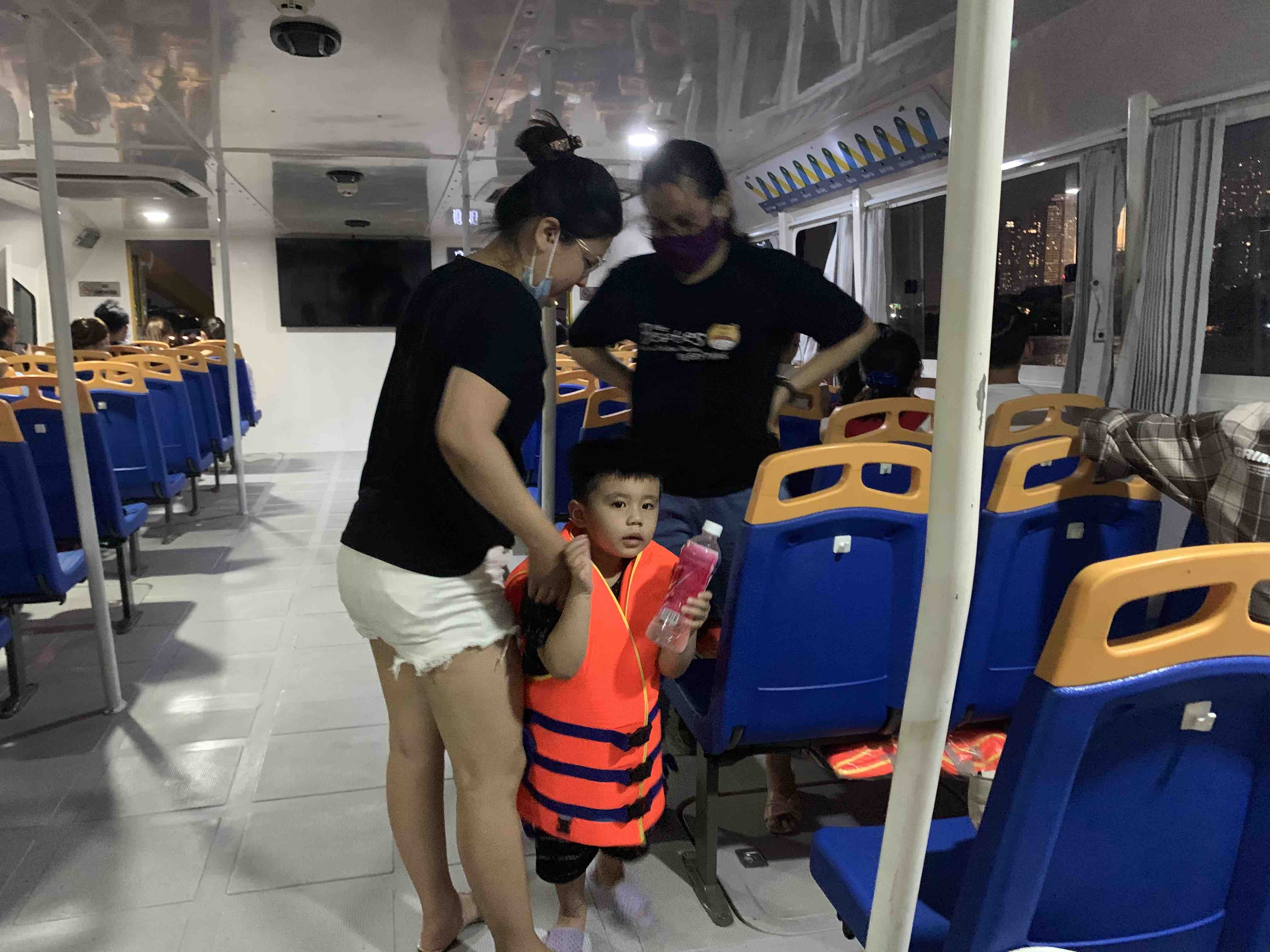 A kid wears life jacket to ensure safety during the trip on the waterbus. Photo: Linh To / Tuoi Tre