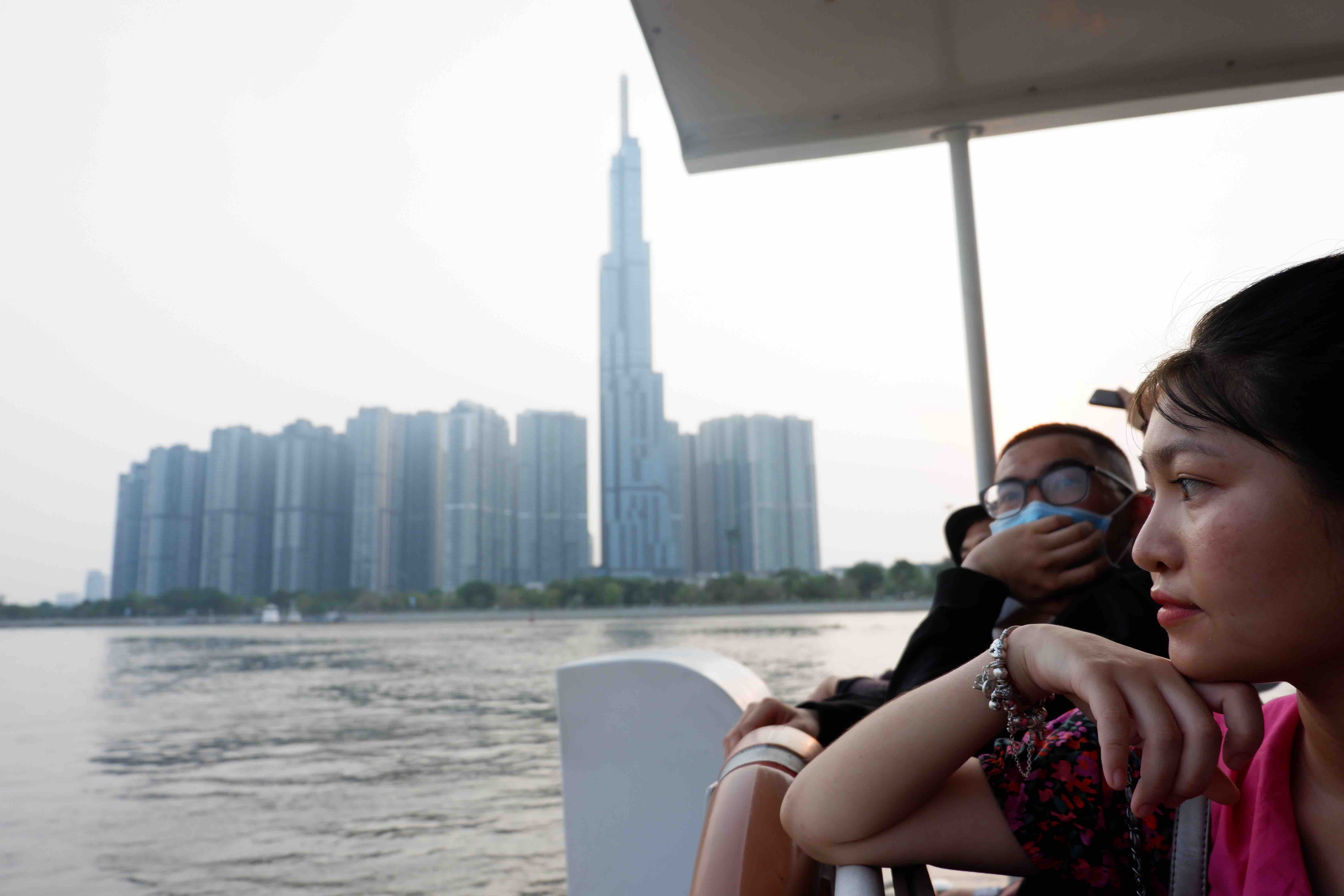 A group of passengers contemplate the sun go down against the blue background of the sky and the iconic Landmark 81 skyscraper in from the Saigon Waterbus. Photo: Linh To / Tuoi Tre