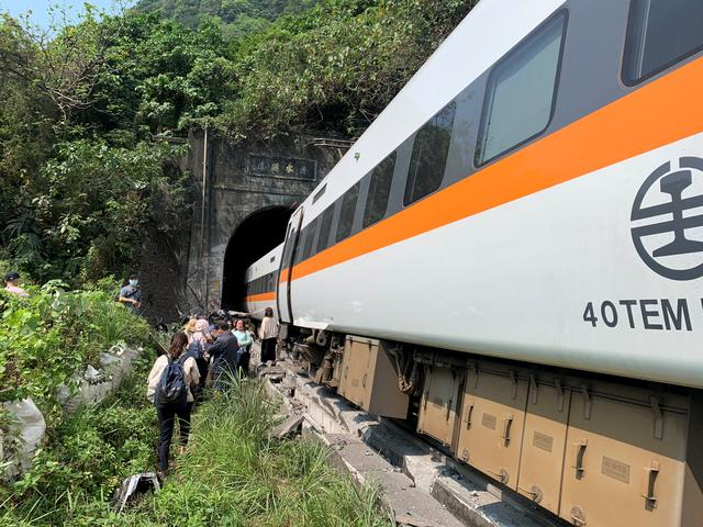 People walk next to a train which derailed in a tunnel north of Hualien, Taiwan April 2, 2021, in this handout image provided by Taiwan's National Fire Agency. Photo: Taiwan's National Fire Agency/Handout via Reuters