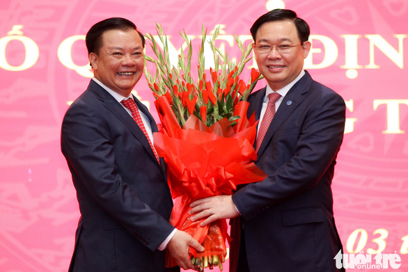 Vietnam's Minister of Finance Dinh Tien Dung (L) takes a bouquet of flowers from Vuong Dinh Hue, chairman of the National Assembly, during a ceremony to receive a Politburo decision to appoint the former as chief of the Hanoi Party Committee in the capital on April 3, 2021. Photo: Nguyen Khanh / Tuoi Tre