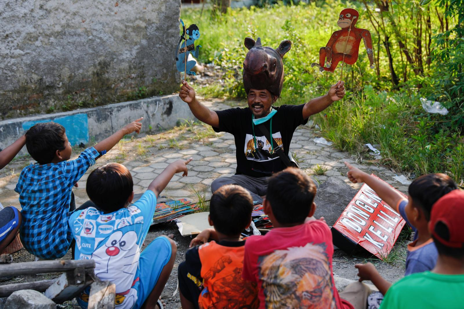Samsudin, 50, wearing a rhino-hat holds cupboard puppets depicting Indonesia's endemic primates orangutan and long tail monkey, while performing fairy tales for the local children in Indramayu regency, West Java province, Indonesia, March 12, 2021. Photo: Reuters