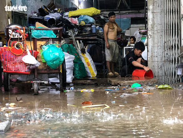 A resident on Nguyen Huu Canh Street in Ho Chi Minh City's Binh Thanh District bails floodwater out of his house, April 4, 2021. Photo: Chau Tuan / Tuoi Tre