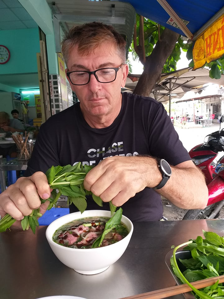 Australian Ray Kuschert is putting veggies into his bowl of pho in a photo he provided Tuoi Tre News