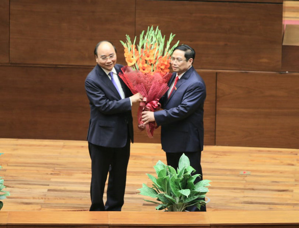 Prime Minister Pham Minh Chinh (R) presents flowers to his predecessor Nguyen Xuan Phuc at the National Assembly in Hanoi, April 5, 2021. Photo: Ngoc Hien / Tuoi Tre