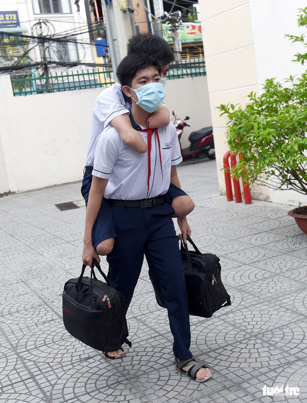 Gia Hung carries Gia Lam on his back with their school bags clutched firmly in his hands when they go to school together. Photo: Duyen Phan / Tuoi Tre