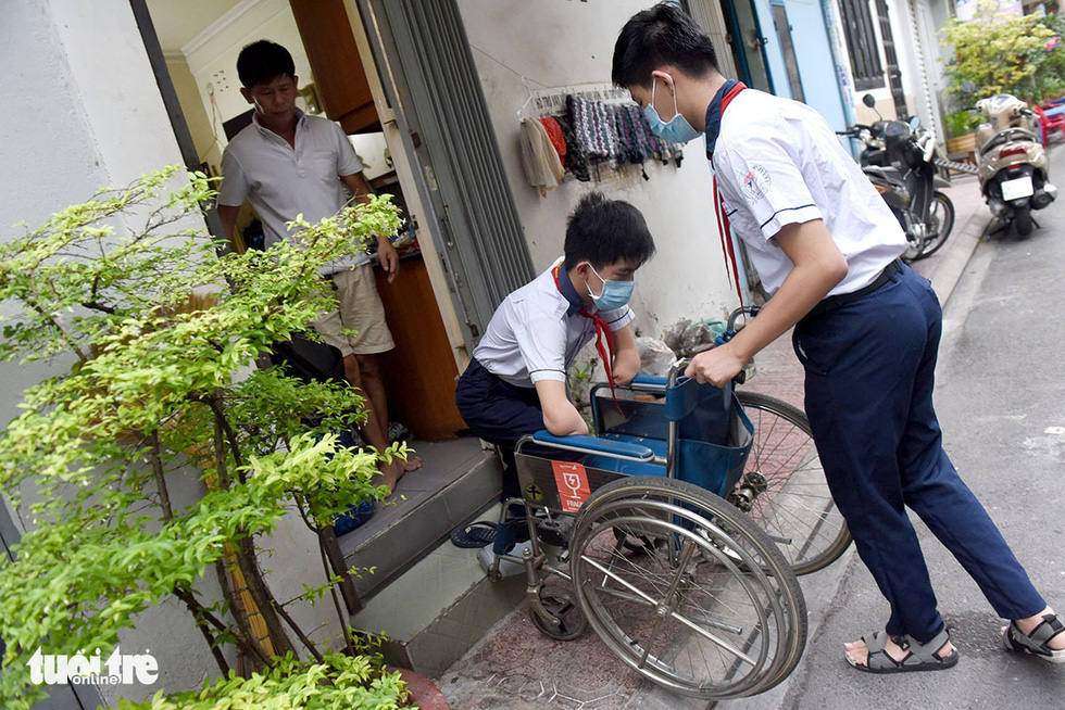 Gia Hung is holding the wheelchair while Gia Lam gets in to go to school. Photo: Duyen Phan / Tuoi Tre