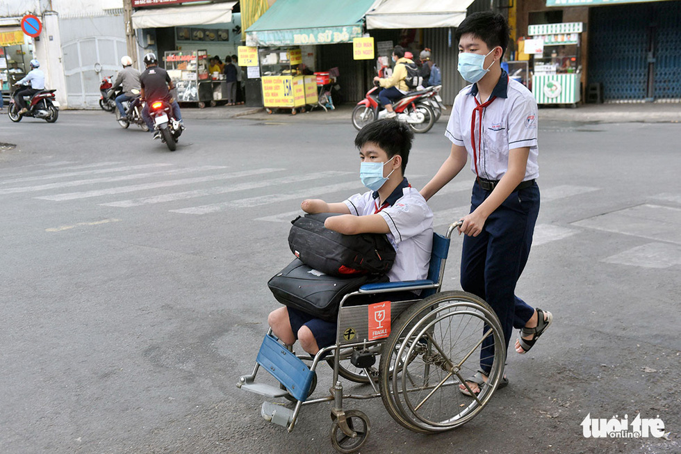 Gia Hung pushes the wheelchair with his younger brother Gia Lam. Photo: Duyen Phan / Tuoi Tre