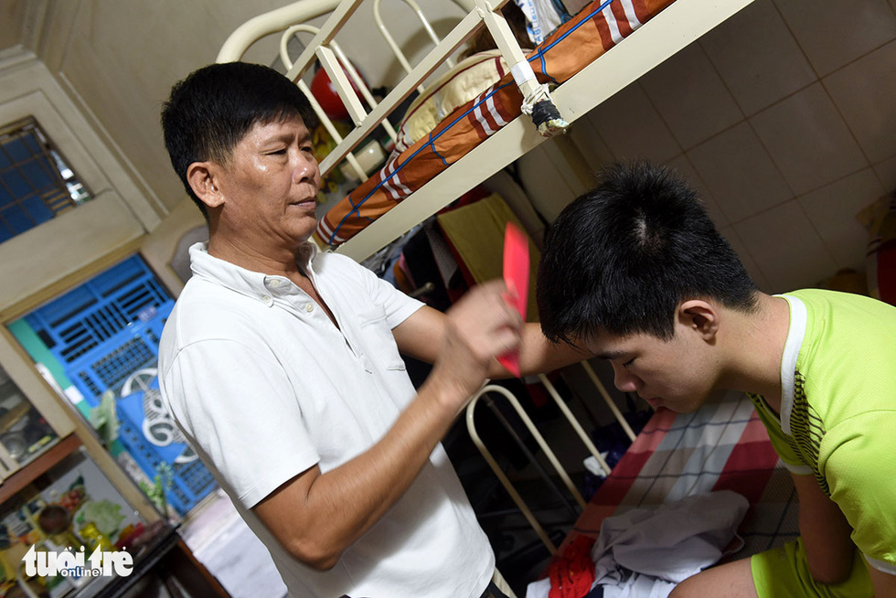 Lap, father of Gia Lam and Gia Hung, combs Lam's hair. Photo: Duyen Phan / Tuoi Tre