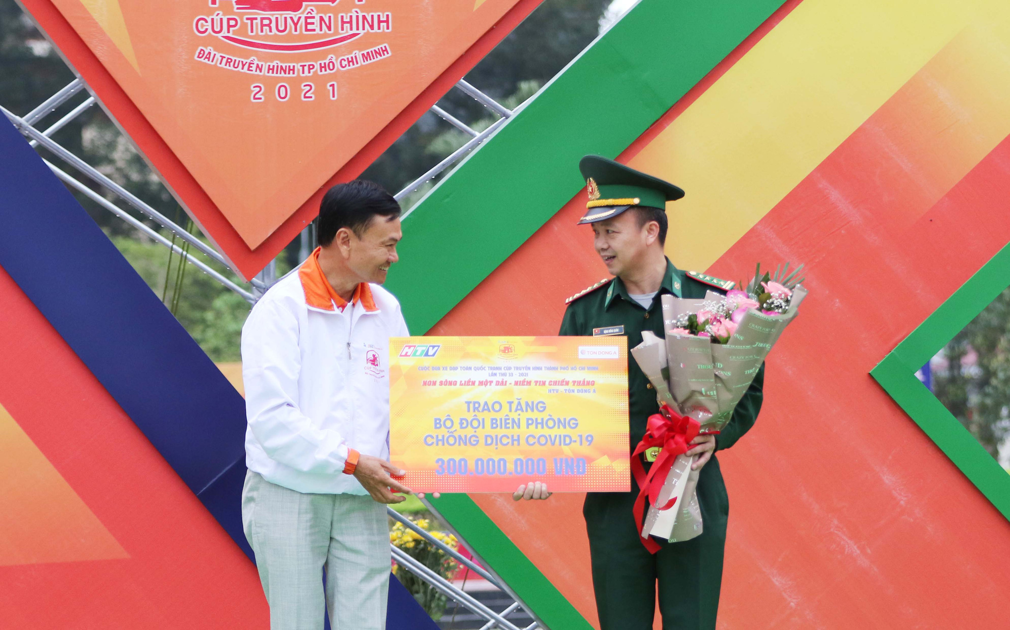A representative of Ton Dong A Corporation (left) hands over the symbolic board of donation to a representative of the Border Guard Command of Cao Bang Province in the opening stage at the HTV Cup national cycling tournament in Cao Bang Province, Vietnam, April 6, 2021. Photo: T.P. / Tuoi Tre
