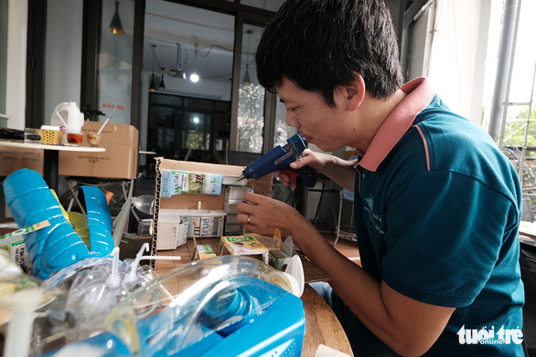 Huy assembles a toy from discards. Photo: Mai Thuong/Tuoi Tre