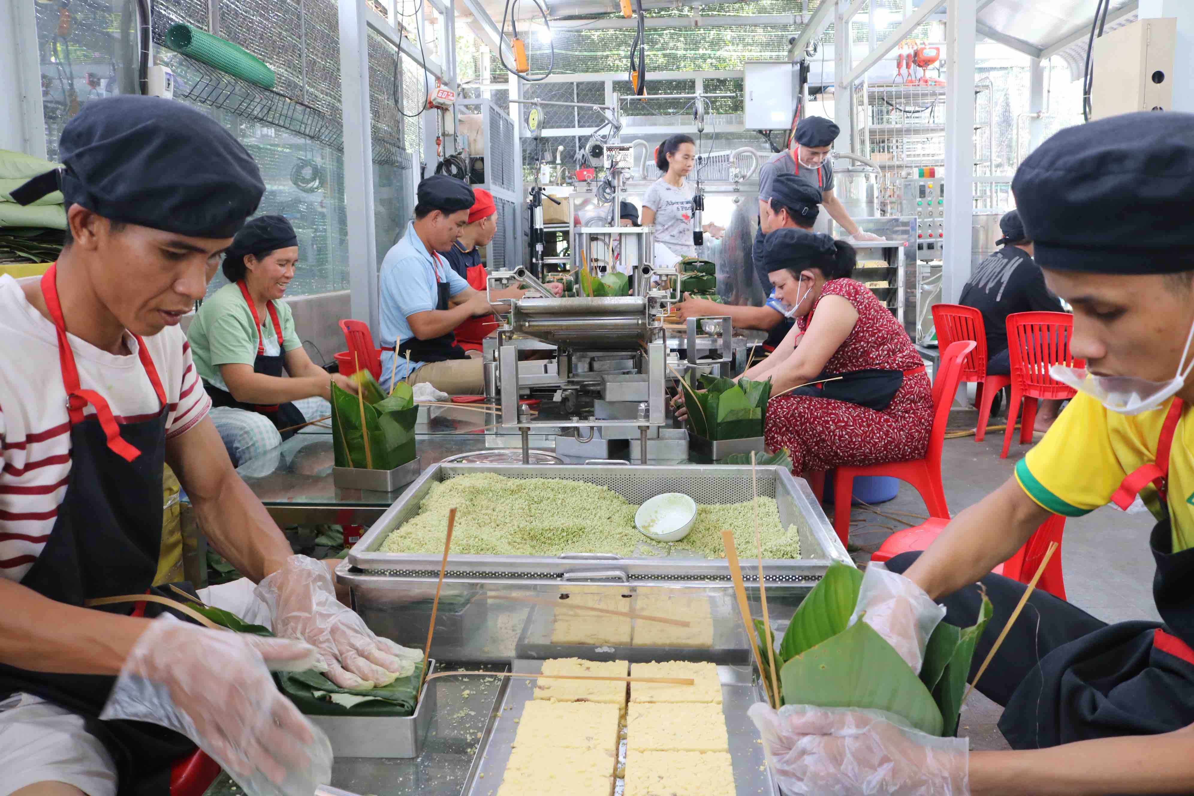 In the photo, the staffs at Pham Khac Tuong's facility wrap 'banh chung' with the help of the machine line at Thu Duc City. Photo: Hoang An / Tuoi Tre