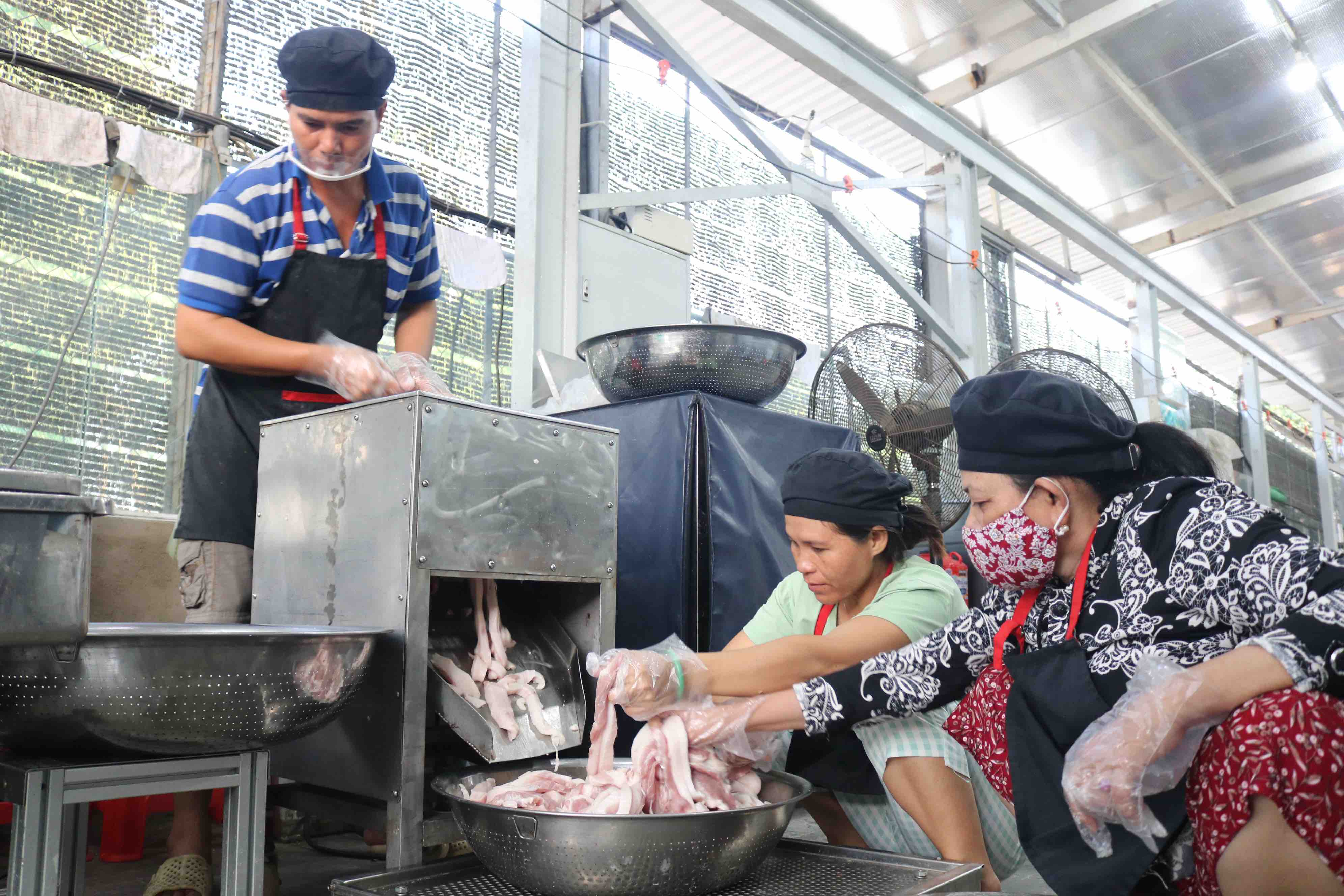Staffs at Pham Khac Tuong's facility put the meat in the blender to cut it into small pieces. Photo: Hoang An / Tuoi Tre