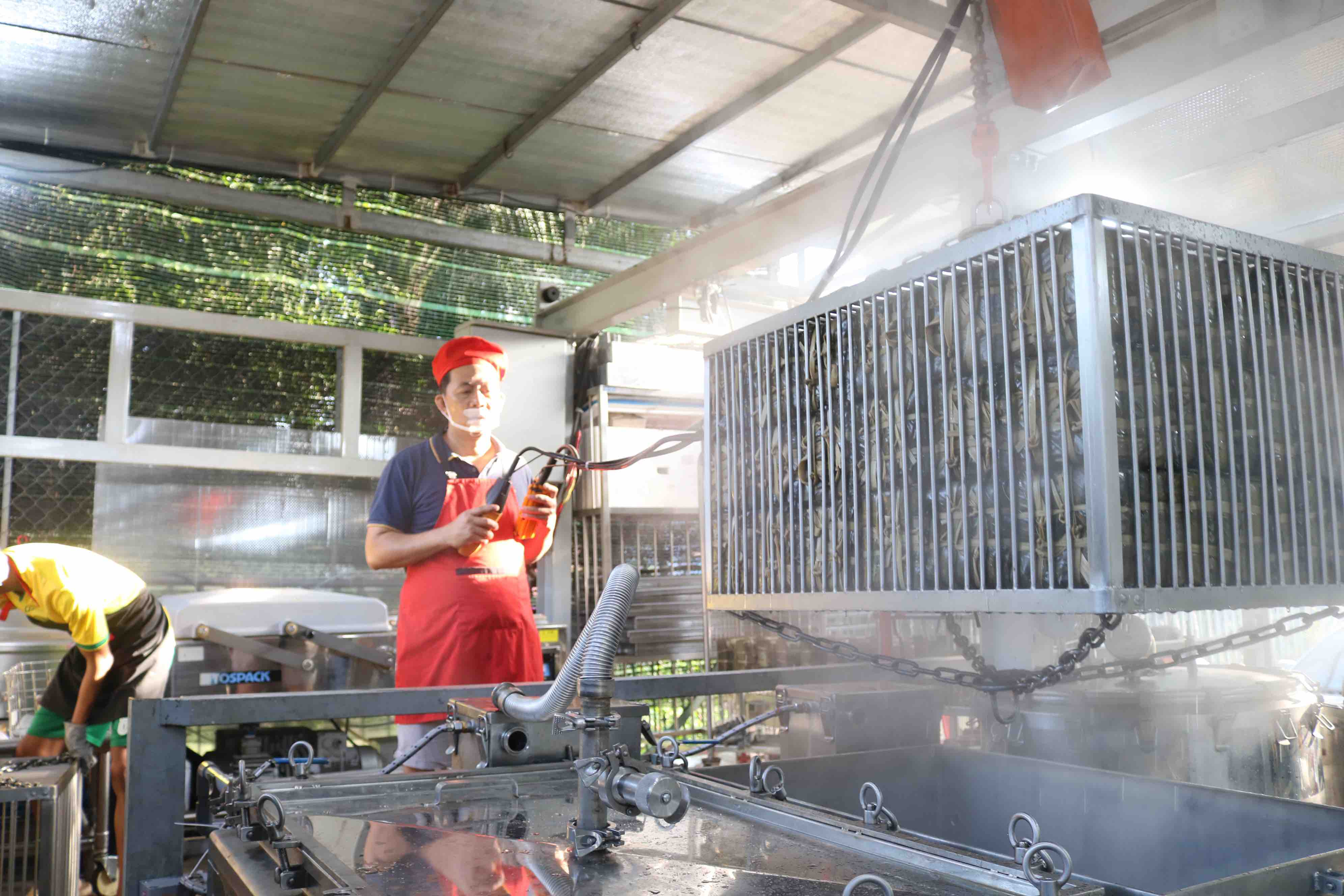 Pham Khac Tuong controls the crane to take out the cooked banh chung. Photo: Hoang An / Tuoi Tre