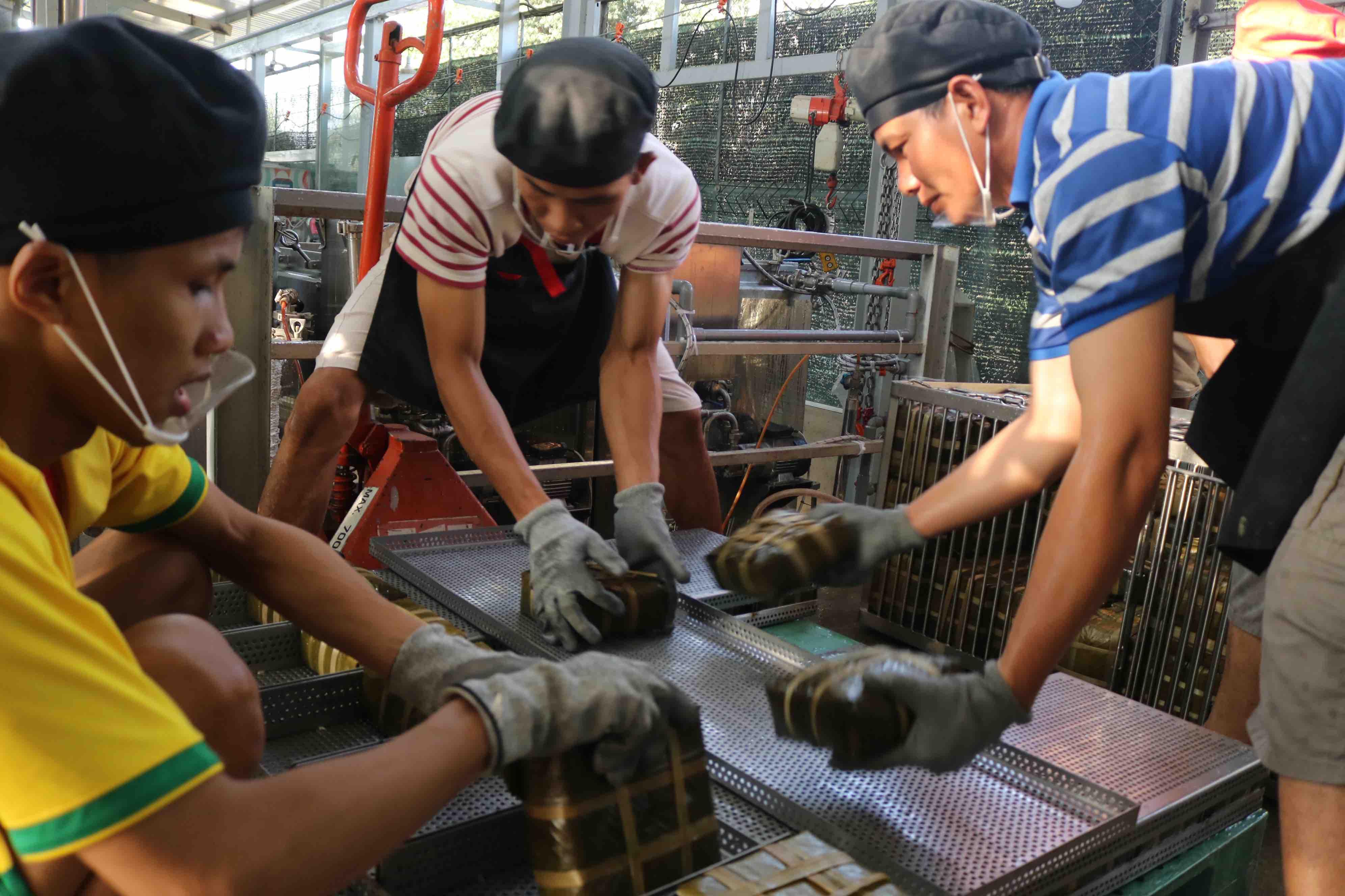 Staff at Pham Khac Tuong's facility arrange the finished banh chung at Thu Duc City. Photo: Hoang An / Tuoi Tre