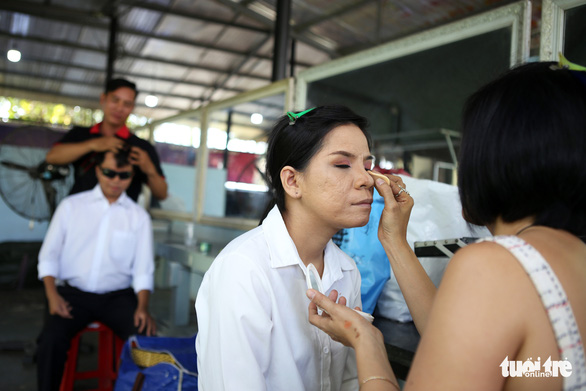 A bride is dressed by a makeup artist. Photo: Nhat Thinh / Tuoi Tre