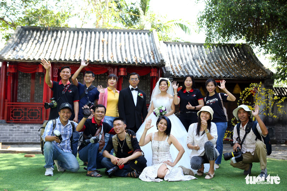 The group takes a photo with the bride and groom after the wedding photoshoot. Photo: Nhat Thinh / Tuoi Tre
