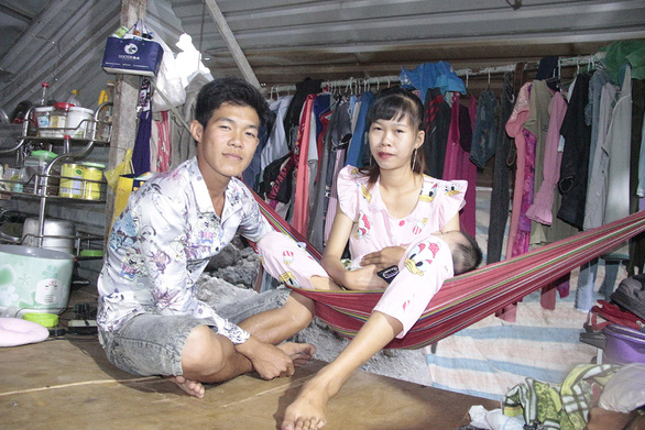 Nguyen Quang Hieu, a young construction worker, poses with his wife and their baby inside the shanty at a building site in Thu Duc City, Ho Chi Minh City. Photo: Cong Trieu / Tuoi Tre