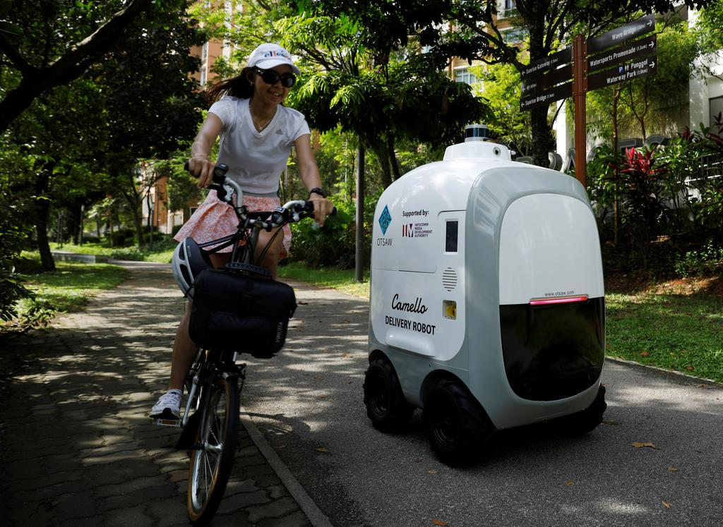 A cyclist passes as Carmello, an autonomous grocery delivery robot, makes its way during a delivery in Singapore April 6, 2021.  Photo: Reuters
