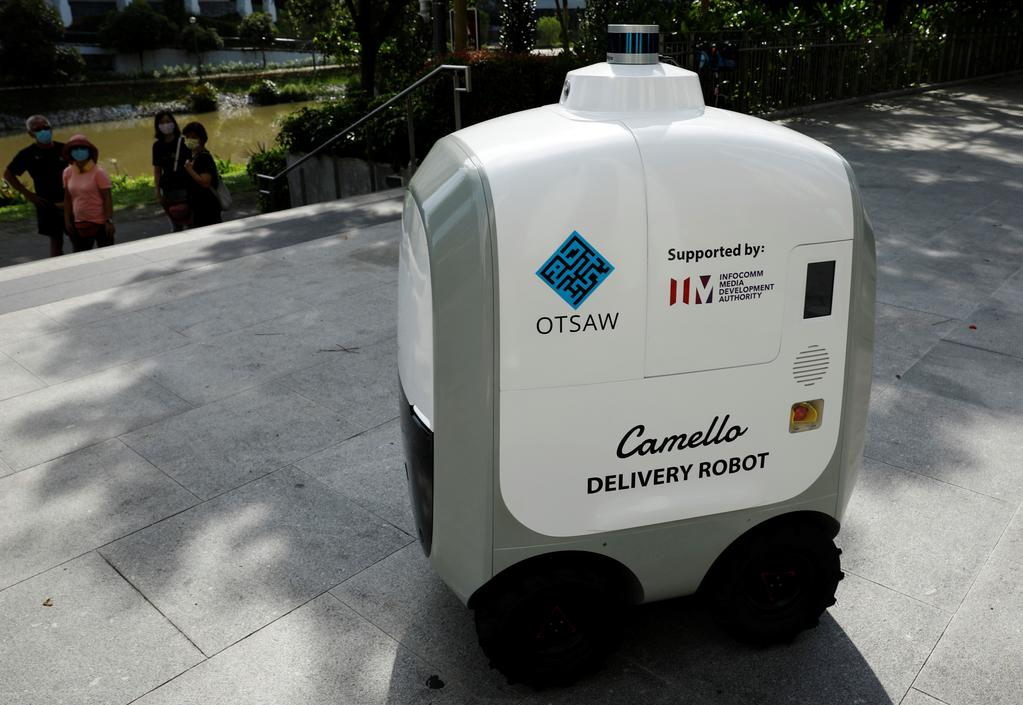 People look on as Carmello, an autonomous grocery delivery robot, makes its way during a delivery in Singapore April 6, 2021. Photo: Reuters