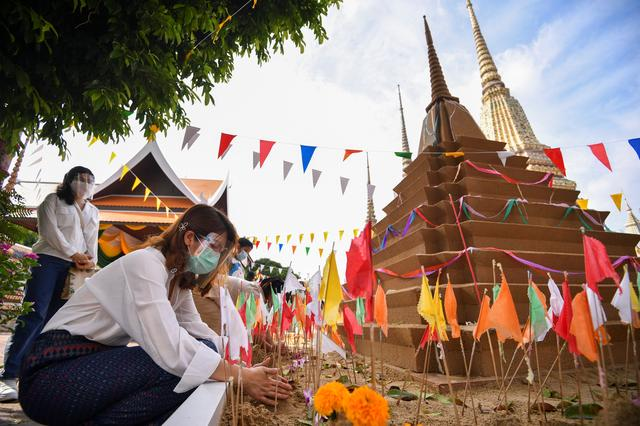 A woman wearing protective face mask makes a sand pagoda during Songkran holiday which marks the Thai New Year during the coronavirus disease (COVID-19) outbreak, as the country deals with a fresh wave of infections after tackling earlier outbreaks, in Bangkok, Thailand, April 13, 2021. Photo: Reuters