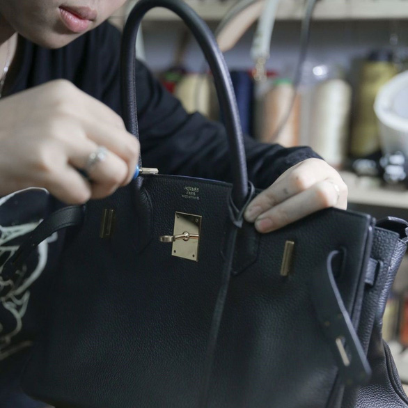 Nguyen Thi Thanh Truc painstakingly repairs a luxurious Hermes bag. – Photo: Le Phan/Tuoi Tre