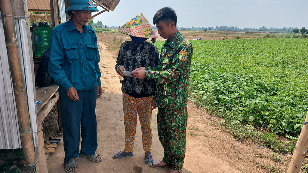 A border guard officer talks with local residents in An Giang Province, Vietnam. Photo: Buu Dau / Tuoi Tre